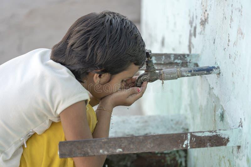 Het portret van dorstig Indisch meisje drinkt water van de openluchtkraan op de straat in Rishikesh, India stock foto
