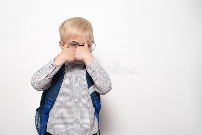 Het portret van een blonde jongen in glazen en met een schoolrugzak op een witte achtergrond toont een gebaarklasse Het concept v royalty-vrije stock foto's