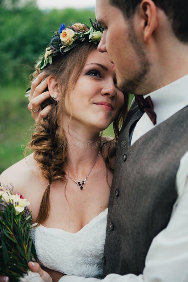 Het portret van een bruid en de bruidegom omhelzen op achtergrondbladerenbos royalty-vrije stock foto