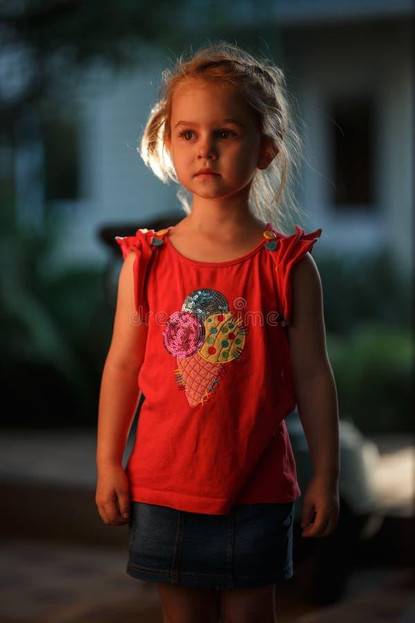 Het portret van een charmant blond meisje die zich buiten op een warme de zomeravond bevinden, de zon verlicht het haar van stock foto's