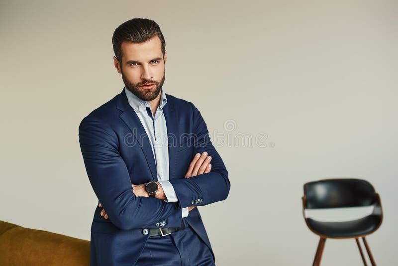 Het portret van een charmante jonge zakenman kleedde zich in kostuum die terwijl status en het bekijken camera zijn modern stelle royalty-vrije stock fotografie