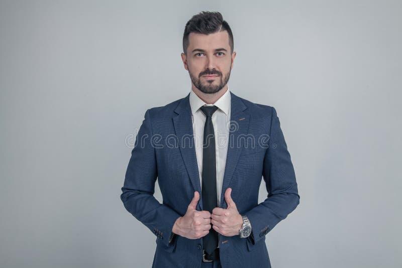Het portret van een charmante rijpe zakenman kleedde zich in kostuum die terwijl status en het bekijken camera over grijs stellen royalty-vrije stock afbeelding