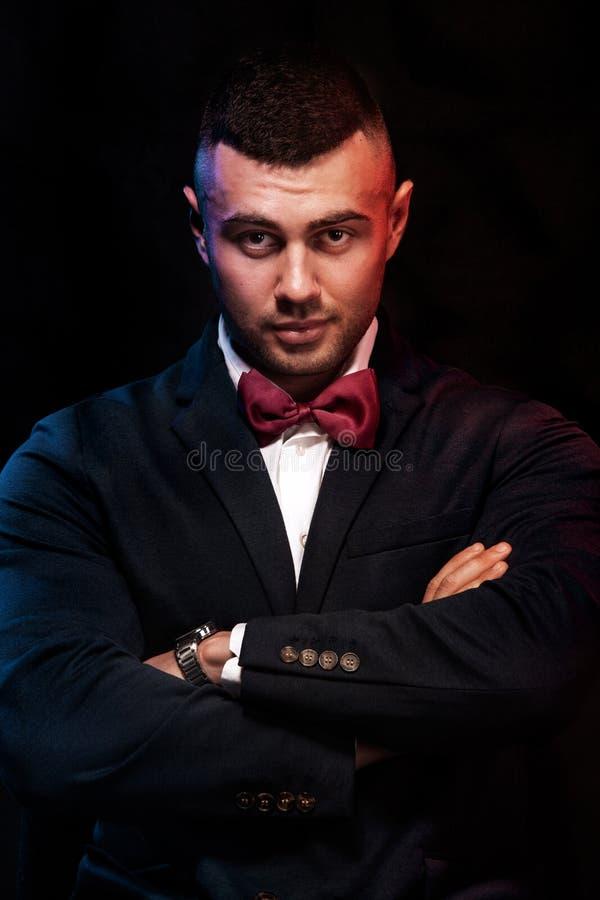 Het portret van een charmante rijpe zakenman kleedde zich in kostuum die terwijl status en het bekijken die camera stellen over z stock afbeeldingen