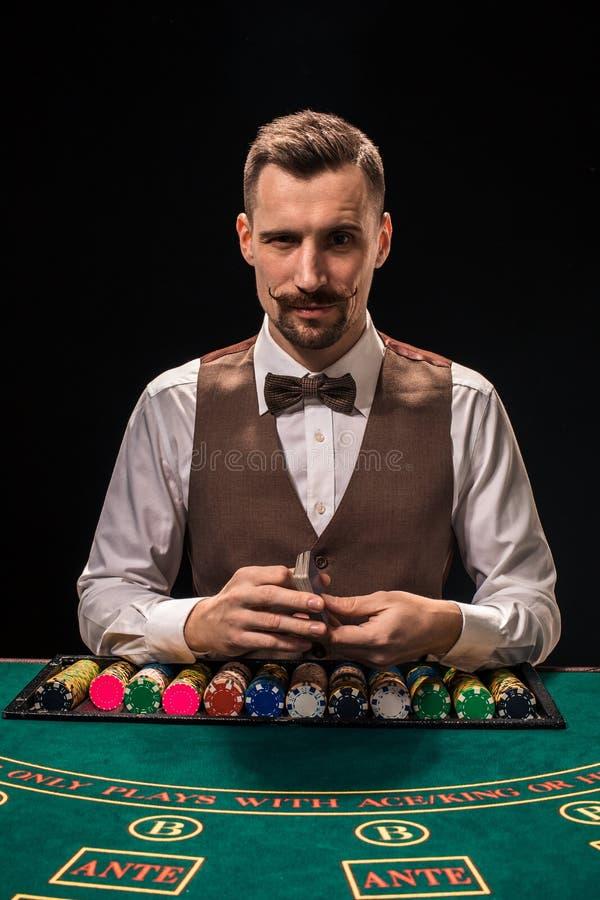 Het portret van een croupier houdt speelkaarten, gokkend spaanders op lijst Zwarte achtergrond royalty-vrije stock foto