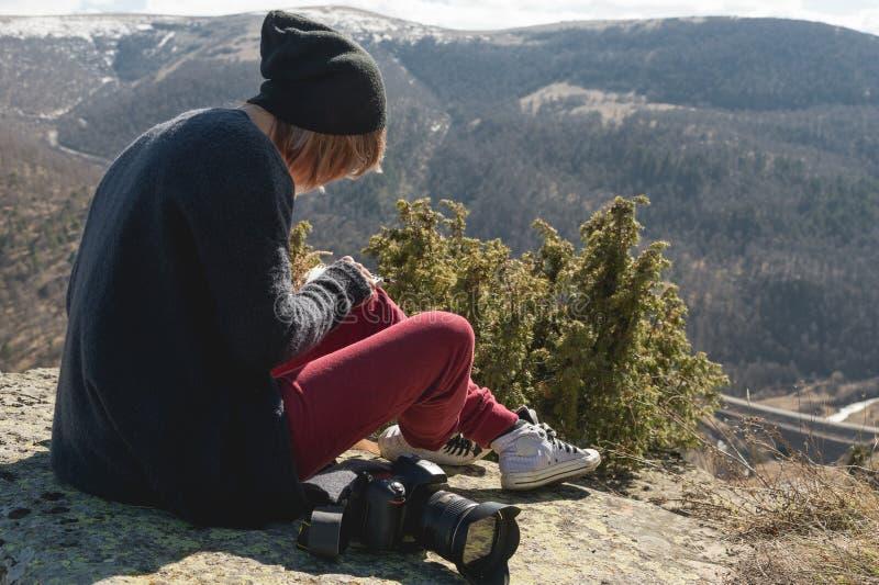 Het portret van een de fotograafmeisje van de hipsterontwerper in hoed en zonnebril trekt een pastelkleur in haar notitieboekjezi stock foto