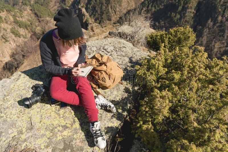 Het portret van een de fotograafmeisje van de hipsterontwerper in hoed en zonnebril trekt een pastelkleur in haar notitieboekjezi stock afbeeldingen
