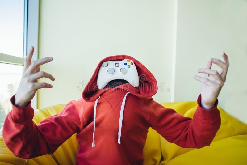 Het portret van een gamer is in plaats daarvan gezicht een bedieningshendel voor videospelletjes Het concept videospelletjes royalty-vrije stock afbeeldingen