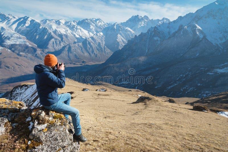 Het portret van een gebaarde mannelijke fotograaf in zonnebril en een warm jasje met een rugzak zit op een grote steen en neemt stock foto's