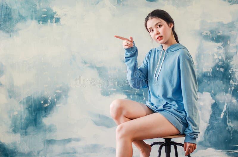 Het portret van een gelukkig jong sportenmeisje die moderne sporten dragen kleedt het benadrukken van vingers één op exemplaarrui royalty-vrije stock fotografie