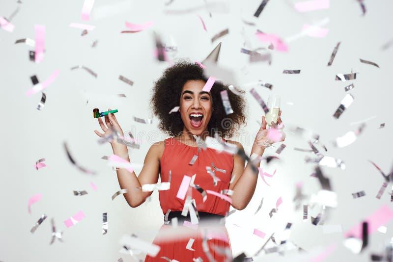 Het portret van een gelukkige afro Amerikaanse vrouw in de holdingsglas van de partijhoed champagne en de partij fluiten, terwijl stock fotografie