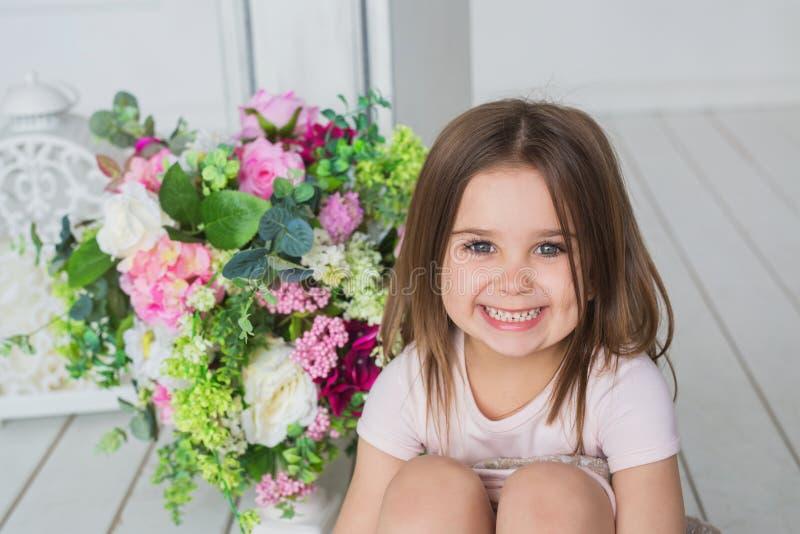 Het portret van een glimlachend meisje in een lichtrose kleding zit op een vloer dichtbij bloemen in een studio stock afbeelding