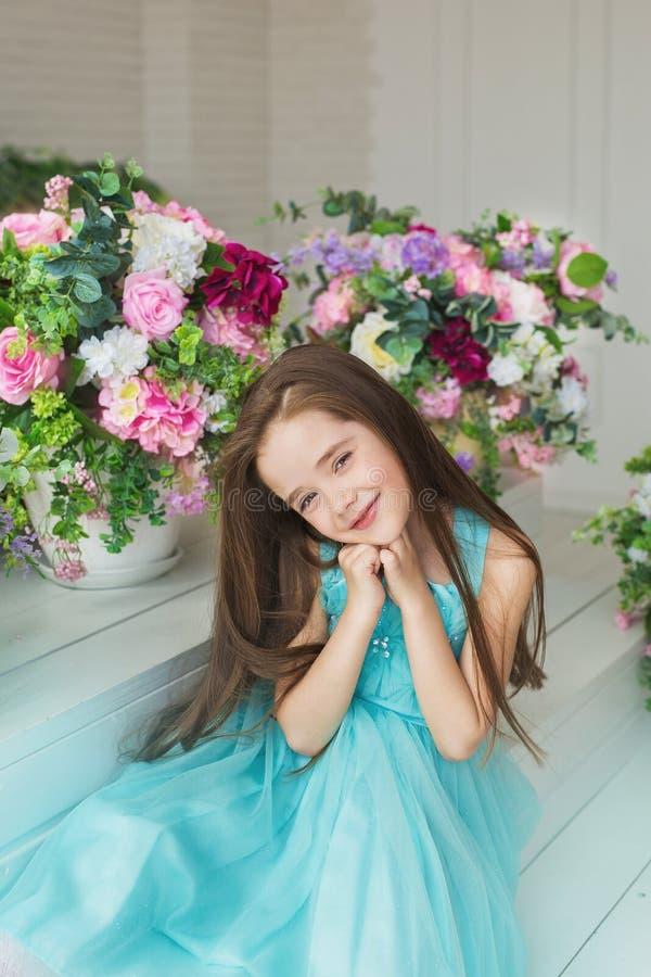 Het portret van een glimlachend mooi meisje in een turkooise kleding in een studio verfraaide bloemen stock foto's