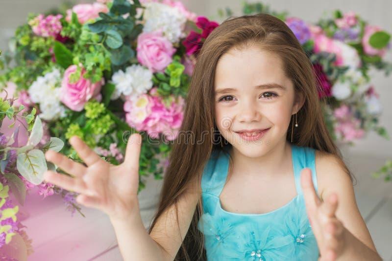 Het portret van een glimlachend mooi meisje in een turkooise kleding houdt handen stand dichtbij bloemen stock afbeelding