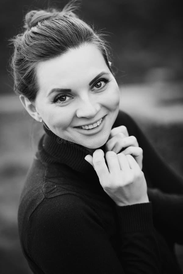 Het portret van een glimlachende mooie zwangere vrouw met het fonkelen bekijkt in een gebreide sweaterholding haar kraag in het p royalty-vrije stock afbeeldingen