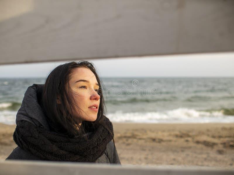 Het portret van een jong meisje met bruine haren bekijkt door een houten omheining op de achtergrond van het overzees stock afbeelding