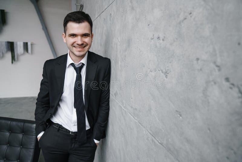 Het portret van een jonge aantrekkelijke mens in een zwart kostuum en de band met een glimlach en zeker zien eruit stock afbeeldingen