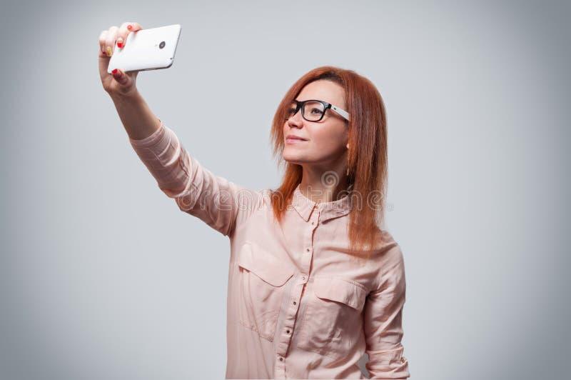 Het portret van een jonge aantrekkelijke vrouw die selfie foto op smartphone maken isoleerde grijze achtergrond royalty-vrije stock afbeelding