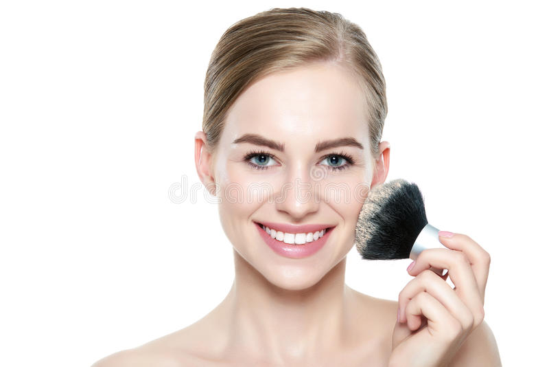 Het portret van een jonge blonde vrouw die droge kosmetische toon- stichting bij haar gezicht het gebruiken toepassen maakt omhoo stock fotografie