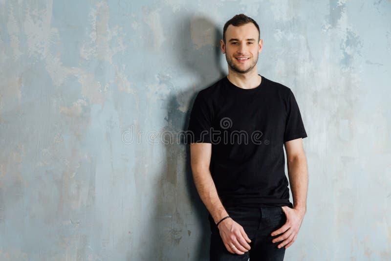 Het portret van een jonge mens in een zwarte T-shirt leunde tegen een uitstekende grijze muur De ruimte van het exemplaar stock afbeeldingen