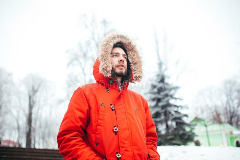 Het portret van een jonge modieuze mens met baard kleedde zich in rood de winterjasje met kap en bont op zijn hoofdtribunes tegen stock foto