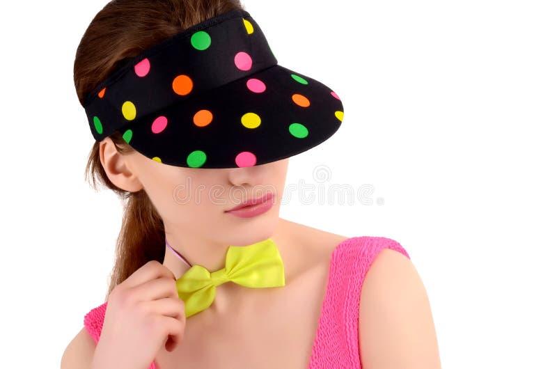 Het portret van een jonge vrouw die een kleurrijke polka draagt stippelde hoed en een neon groene bowtie. stock fotografie