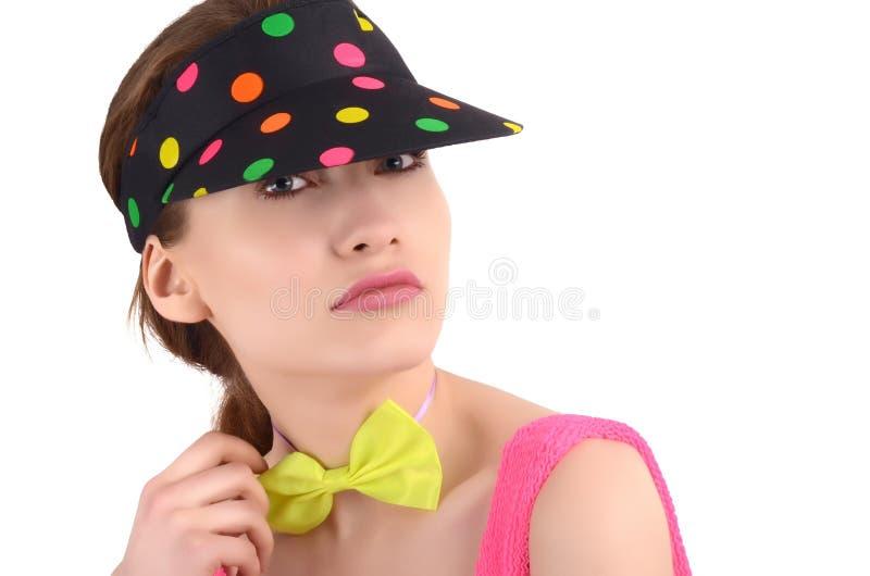 Het portret van een jonge vrouw die een kleurrijke polka dragen stippelde hoed en een neon groene bowtie. stock fotografie