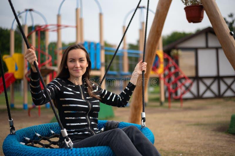 Het portret van een jonge vrouw die op een hangende schommeling slingeren die, concept vrijheid, dag, herinnert kinderjaren weg g royalty-vrije stock foto's