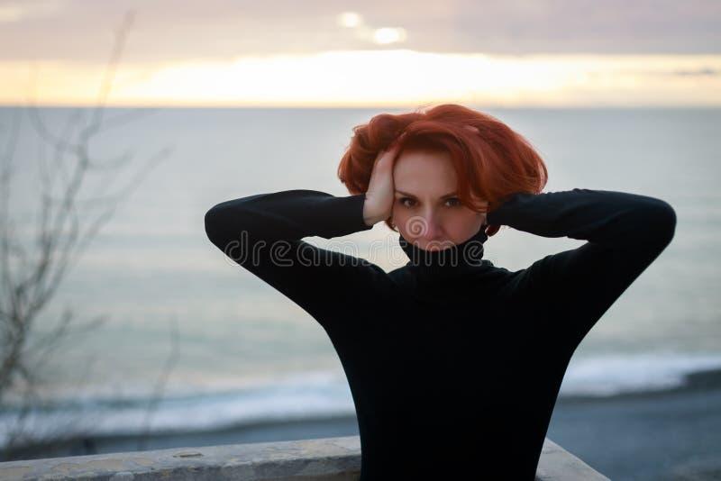 Het portret van een jonge vrouw met rood haar en het doordringen kijken op de achtergrond van het overzees en de zonsondergang royalty-vrije stock fotografie