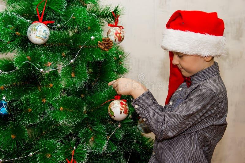 Het portret van een jongen met grappige glazen en het Kerstmisspeelgoed die cristmasboom verfraaien en hebben pret stock fotografie