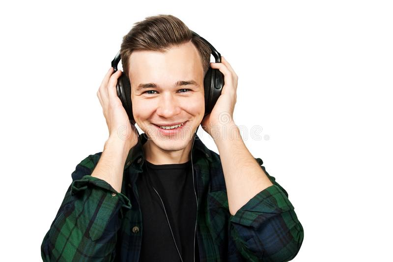 Het portret van een Kaukasische Witte jonge kerel luistert muziek in de oortelefoons De knappe mens kleedde zich in een zwarte T- stock fotografie