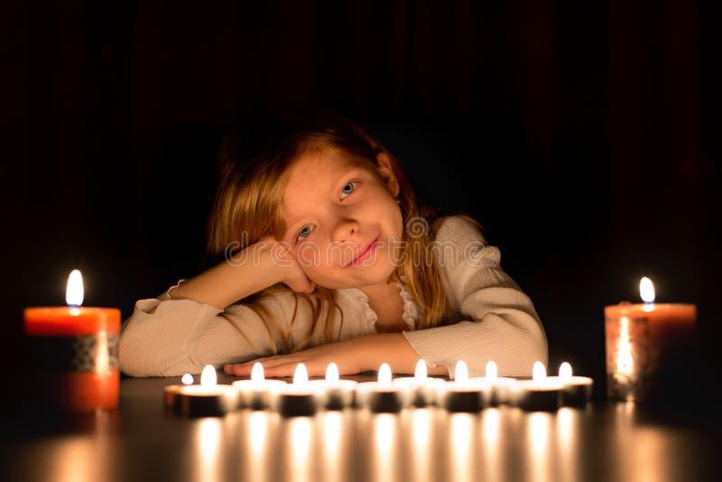 Het portret van een klein blonde Kaukasisch meisje zet in dark rond de kaarsen Zij kijkt vooruit stock fotografie