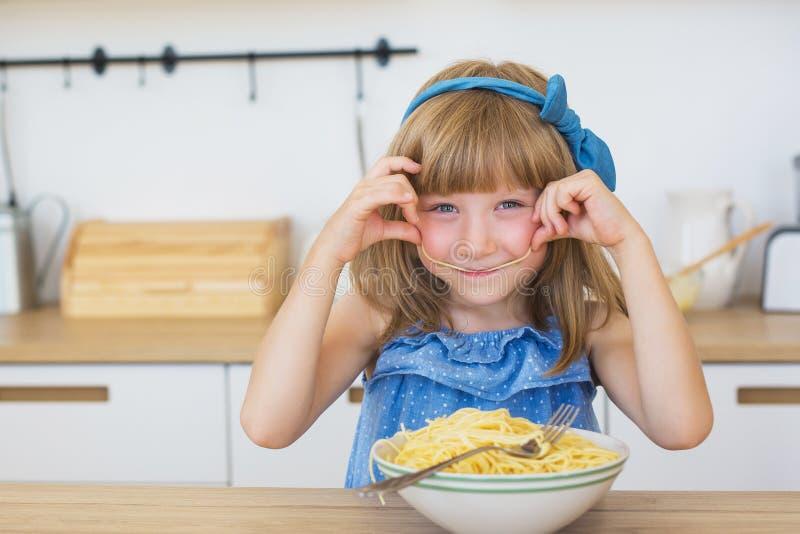 Het portret van een klein grappig meisje eet een spaghetti van een schotel en het glimlachen stock foto's