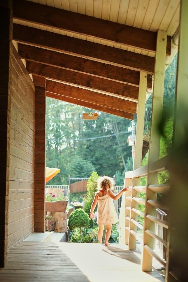 Het portret van een klein meisje dat buiten langs de veranda, de zonneschijnzomer loopt, het meisje gaat voor een gang royalty-vrije stock foto's