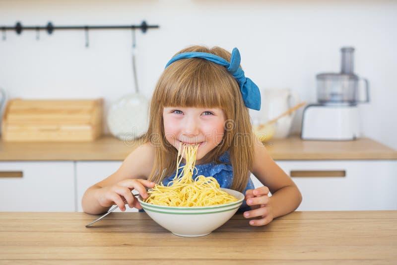 Het portret van een klein meisje in een blauwe grappige kleding eet een spaghetti van een schotel en het glimlachen stock fotografie