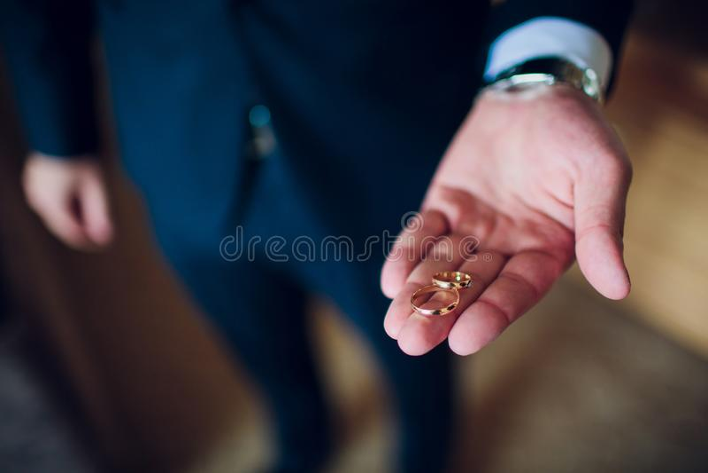 Het portret van een knappe gelukkige mens kleedde zich in smoking houdend open doos met een verlovingsring royalty-vrije stock afbeeldingen