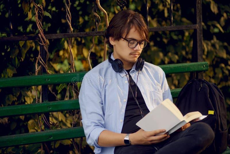 Het portret van een knappe jonge die mens in oogglazen en hoofdtelefoons, las een boek buiten, op een stedelijke parkachtergrond  stock foto