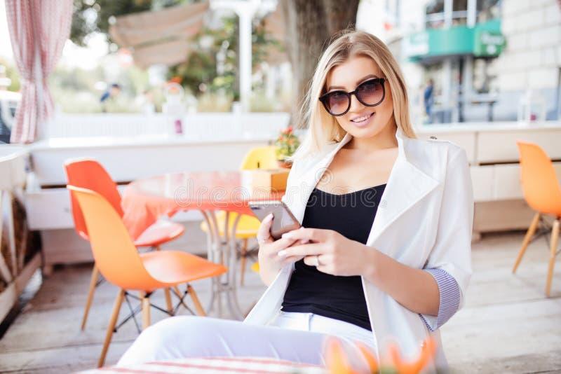Het portret van een leuk blondewijfje las iets op haar slimme telefoon terwijl het zitten in moderne koffiewinkel, mooie jonge hi royalty-vrije stock afbeelding