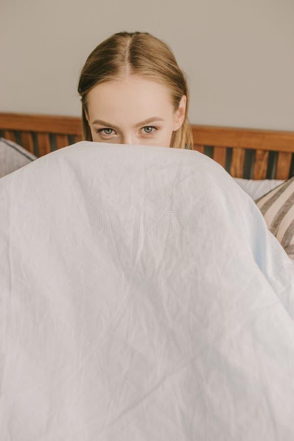 Het portret van een leuk meisje rust op het bed in haar slaapkamer en scherm zelf achter de lichtblauwe deken stock foto's