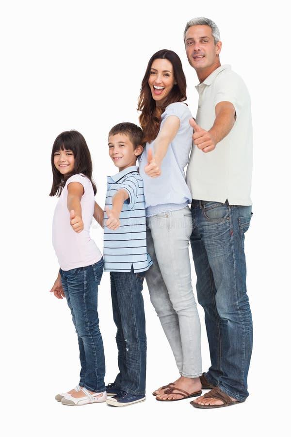 Het portret van een leuke familie in enig dossier die duimen doen omhoog bij kwam royalty-vrije stock foto's