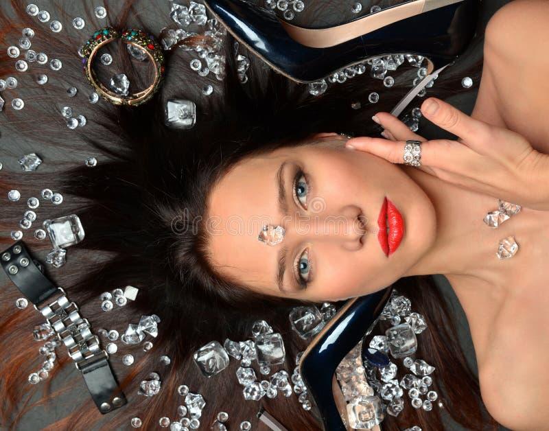 Het portret van een luxueus donkerbruin meisje ligt in een placer van diamantenjuwelen, luxetoebehoren stock foto's