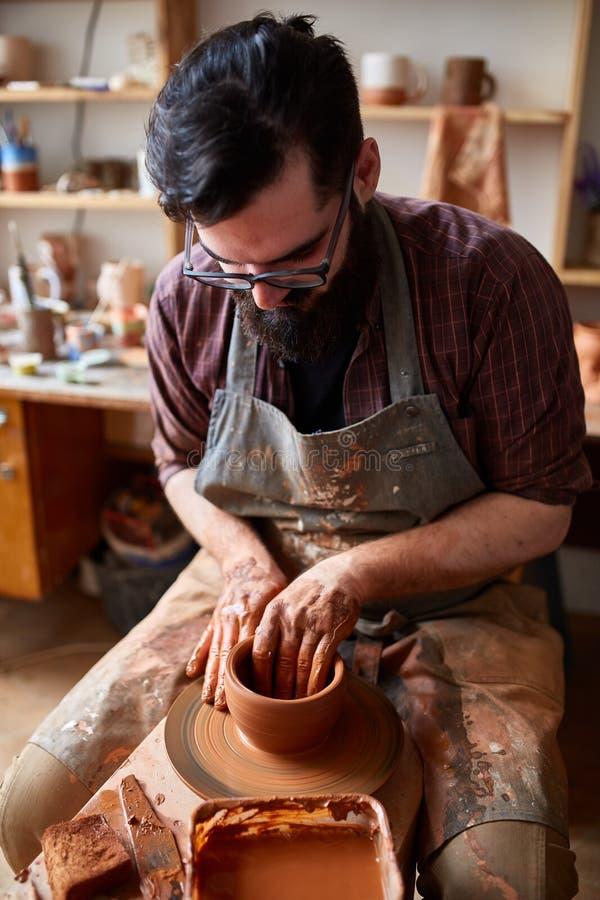 Het portret van een mannelijke pottenbakker in schortvormen werpt van klei, selectieve nadruk, close-up stock afbeeldingen
