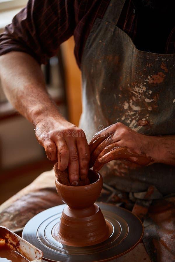 Het portret van een mannelijke pottenbakker in schortvormen werpt van klei, selectieve nadruk, close-up stock fotografie