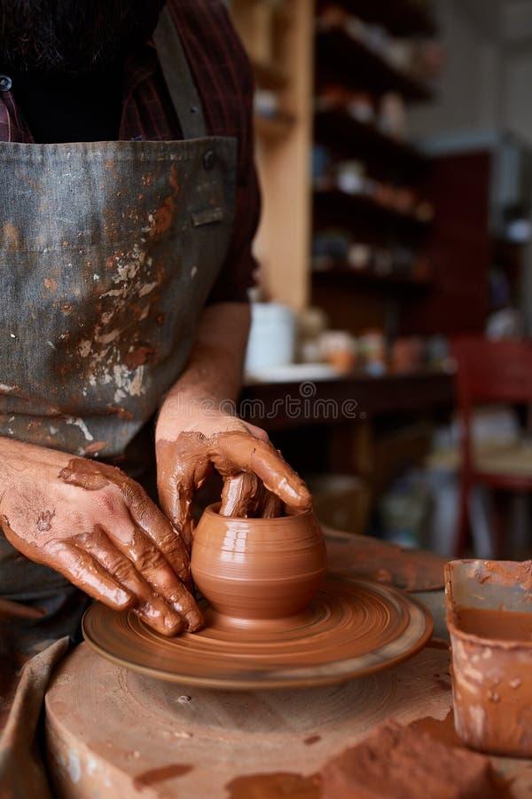 Het portret van een mannelijke pottenbakker in schortvormen werpt van klei, selectieve nadruk, close-up royalty-vrije stock afbeeldingen