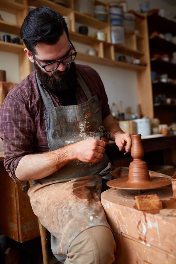 Het portret van een mannelijke pottenbakker in schortvormen werpt van klei, selectieve nadruk, close-up royalty-vrije stock afbeelding
