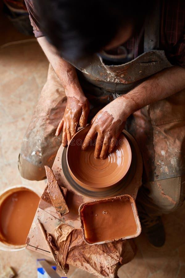 Het portret van een mannelijke pottenbakker in schortvormen werpt van klei, selectieve nadruk, close-up royalty-vrije stock foto's