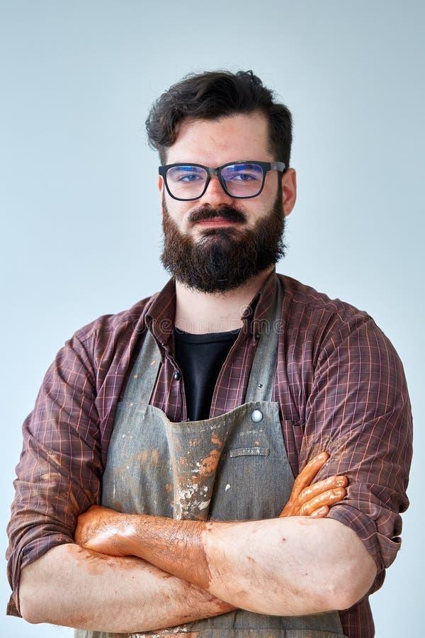 Het portret van een mannelijke pottenbakker in schortvormen werpt van klei, selectieve nadruk, close-up stock foto