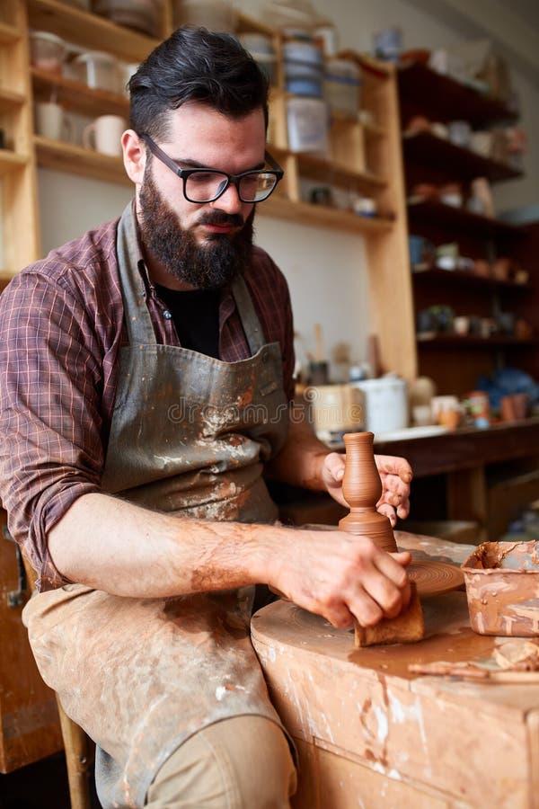 Het portret van een mannelijke pottenbakker in schortvormen werpt van klei, selectieve nadruk, close-up stock afbeelding