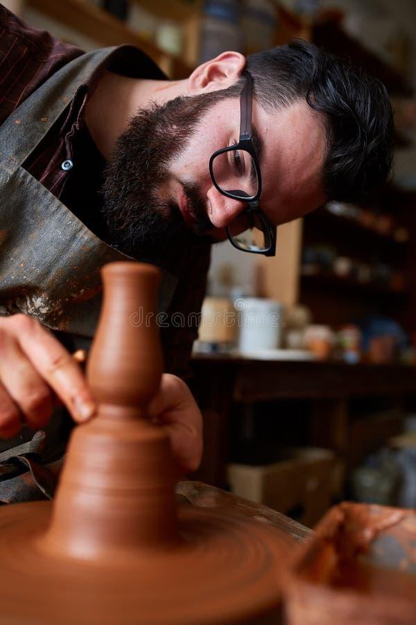 Het portret van een mannelijke pottenbakker in schortvormen werpt van klei, selectieve nadruk, close-up royalty-vrije stock fotografie