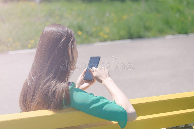 Het portret van een meisje erachter op een gele bank en geniet van smartphone, online mededeling, sociale netwerken, corresponden royalty-vrije stock foto