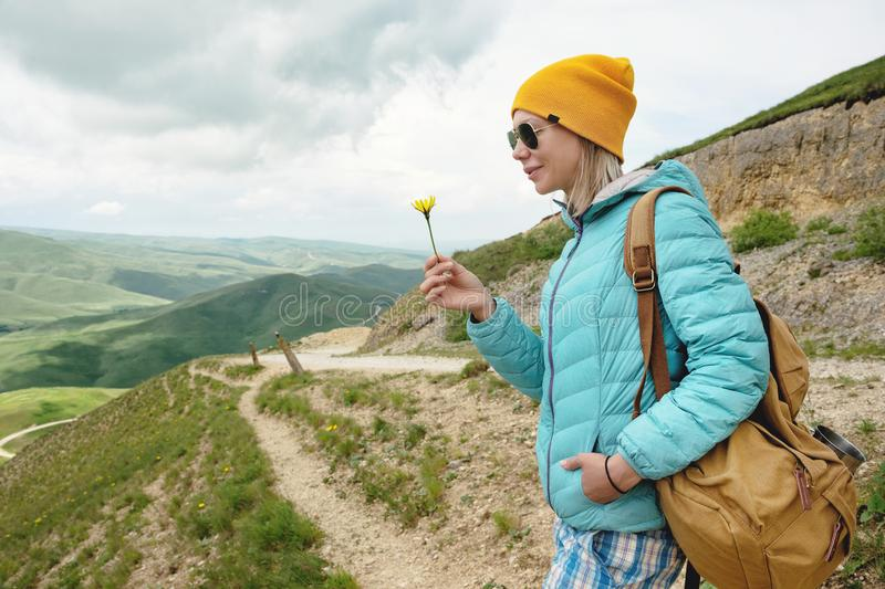 Het portret van een meisje in een hoed en zonnebril houdt een bloem in de vroege lente op aard Het concept eenheid met royalty-vrije stock afbeeldingen